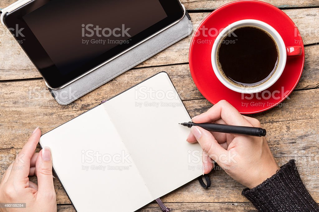Young woman writing or drawing into notepad stock photo