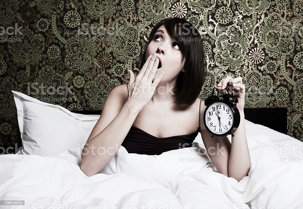 Young Woman Yawning in Bed stock photo
