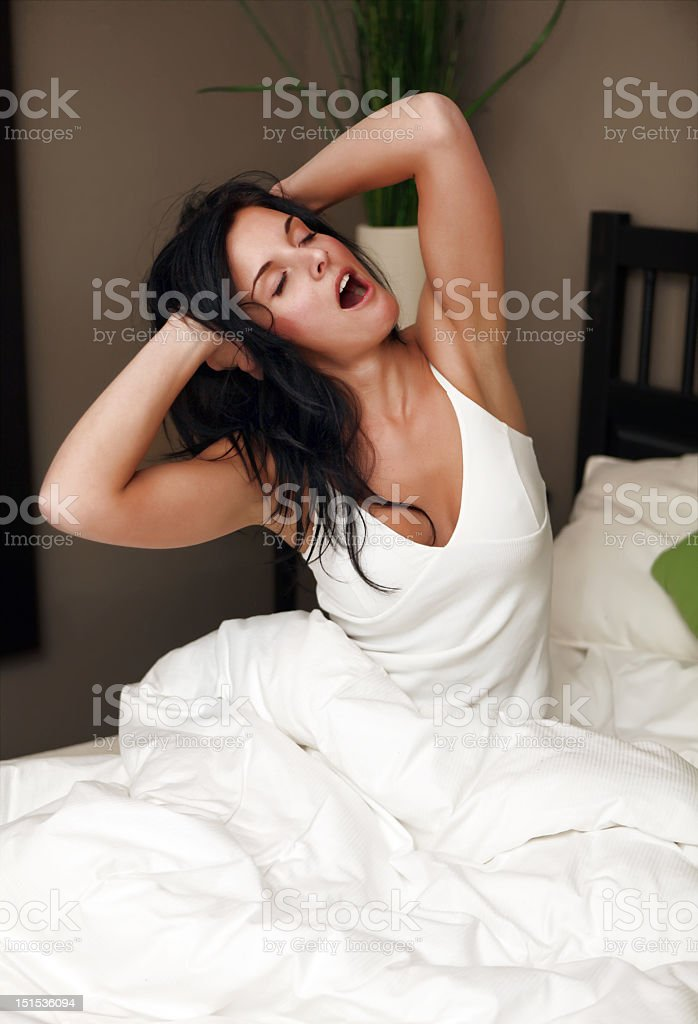 Young woman yawning in bed royalty-free stock photo