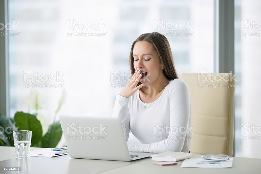 Young woman yawning near laptop stock photo
