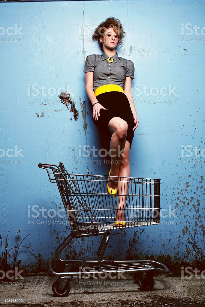 Young Woman Yellow Pumps and Belt Standing in Shopping Cart royalty-free stock photo