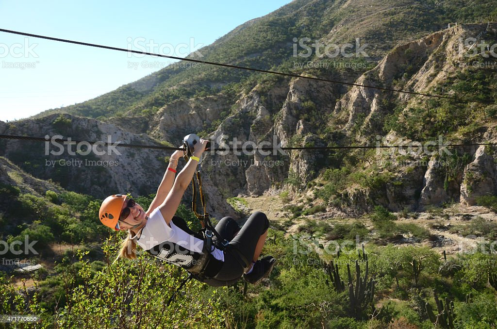 Young Woman Zip-Lining in Cabo San Lucas, Mexico. stock photo