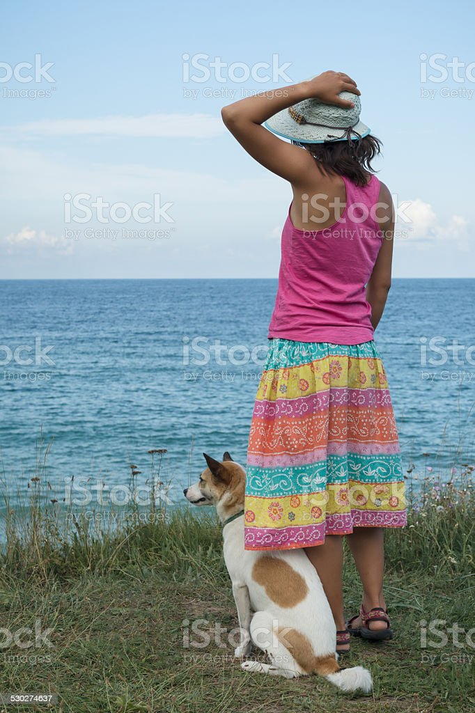 young womand and dog watching the sea stock photo