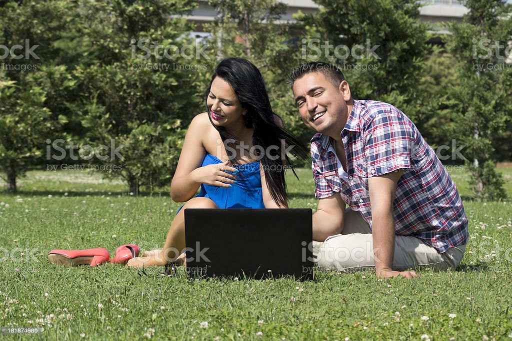 Young womann and man using laptop in park royalty-free stock photo