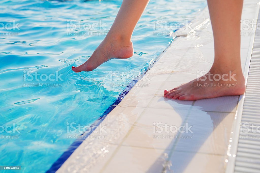 Young woman's feet dipping slowly in the water stock photo