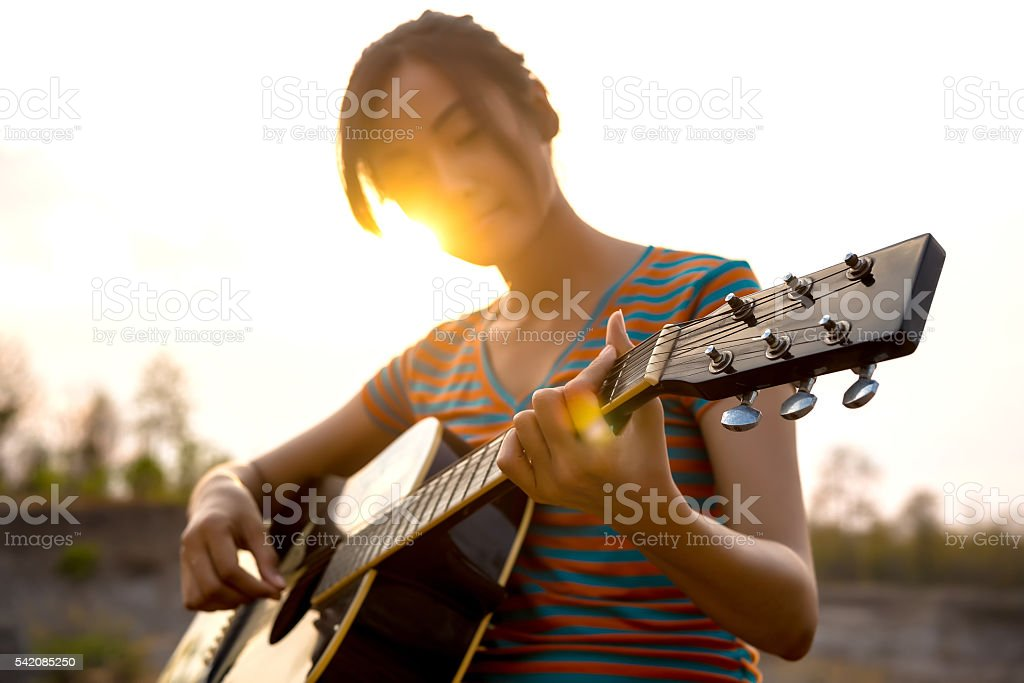Young Woman's Hand Playing guitar. outdoors stock photo