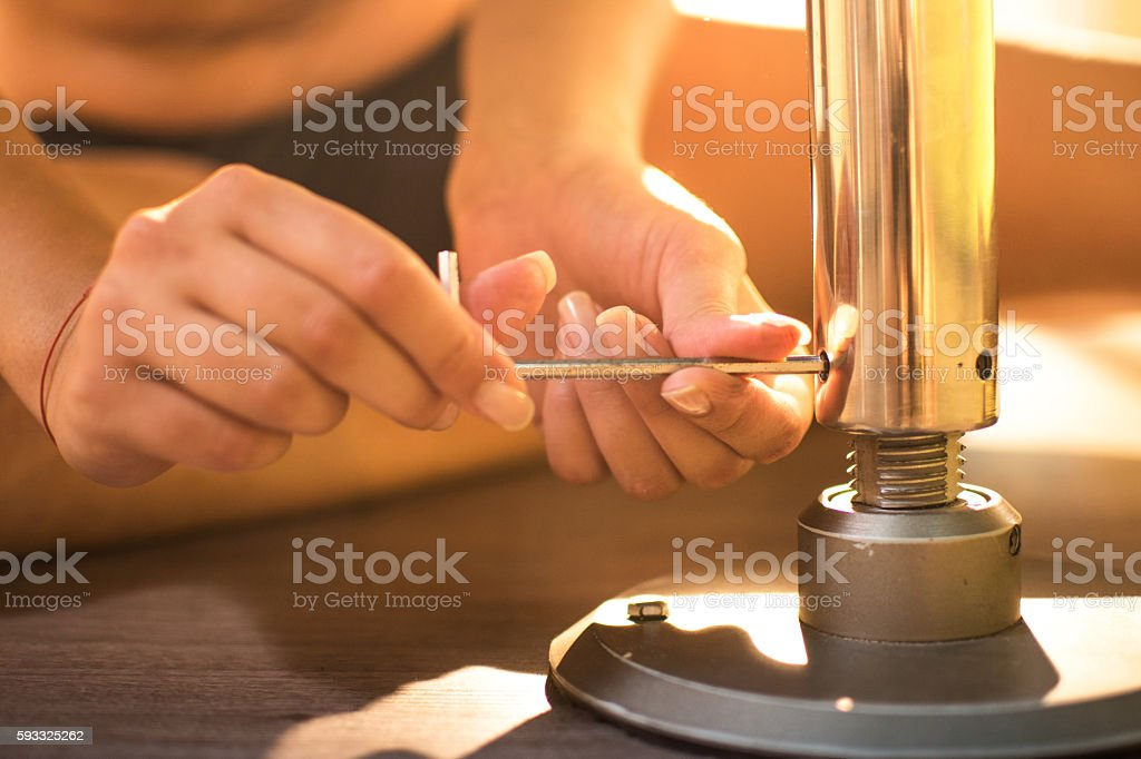 Young woman's hands adjusting a pole using hexagonal key tool. stock photo