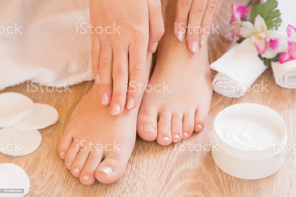 Young woman's hands applying a foot moisturizing cream. Pedicure beauty salon. stock photo