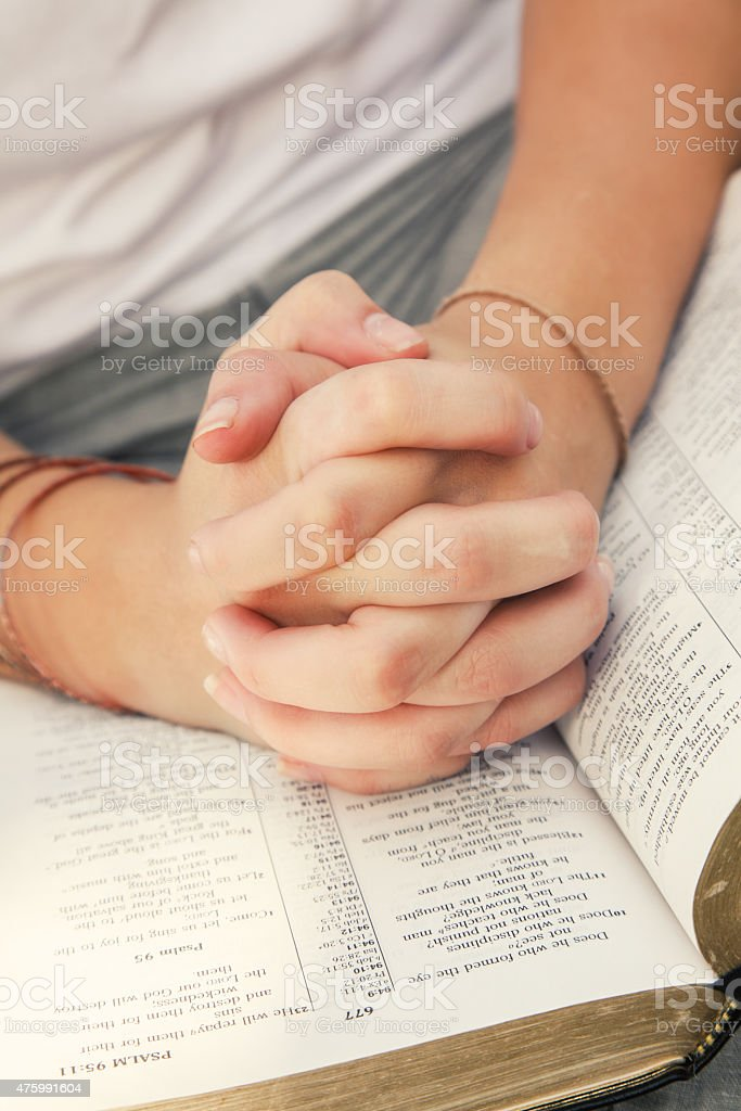 Young woman's hands folded in prayer on top of Bible stock photo