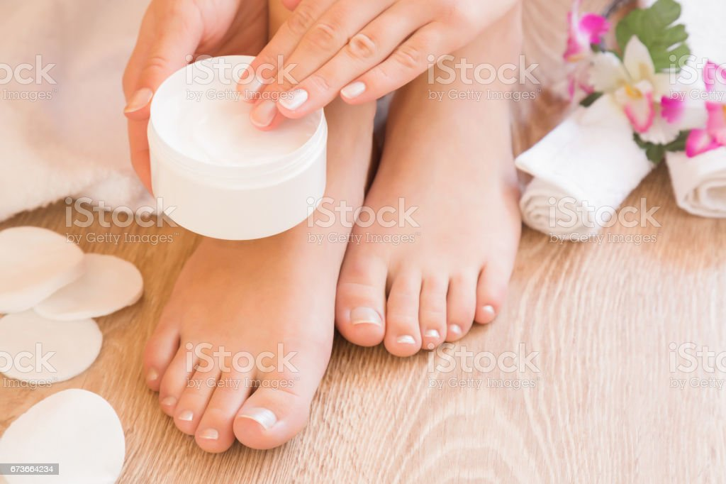 Young woman's hands holding a jar of foot moisturizing cream. Pedicure beauty salon. stock photo