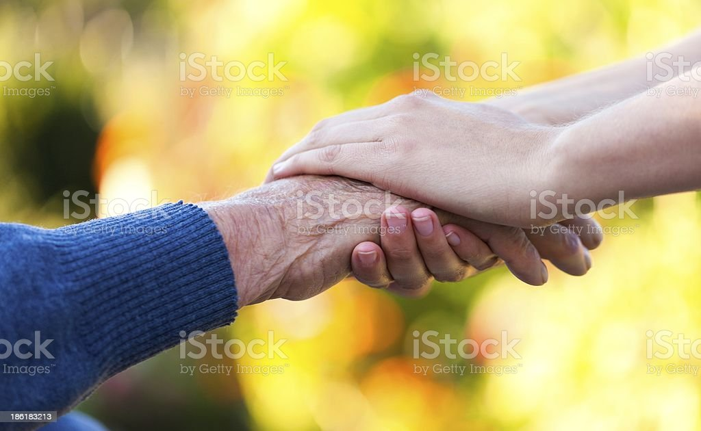 Young woman's hands holding old man's hands stock photo