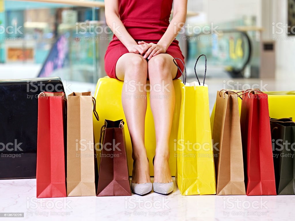 young woman's legs and colorful shopping bags stock photo