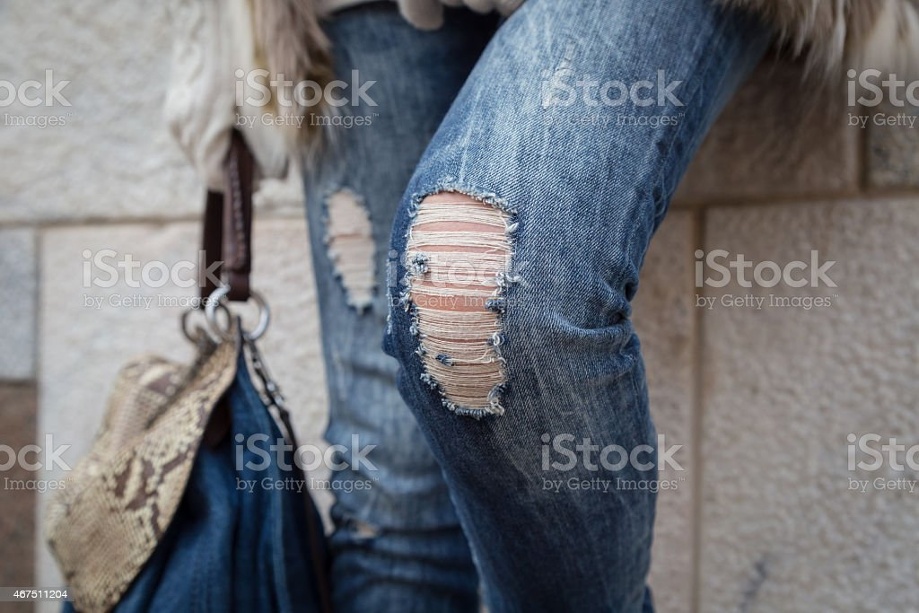 Young woman's legs with jeans ripped at the knees stock photo
