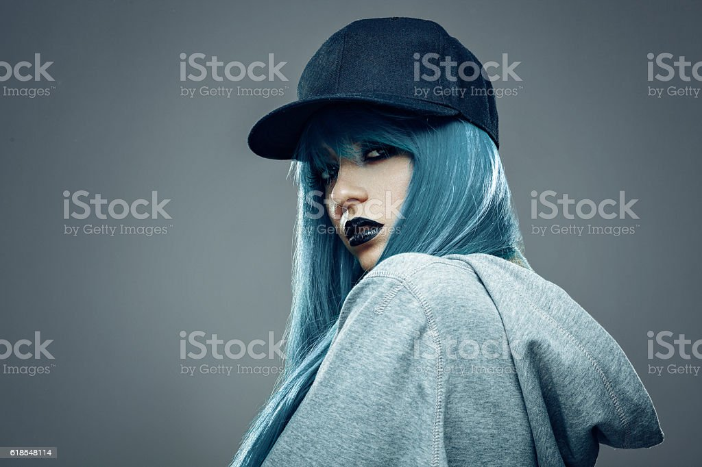 Young womanwith cyan color hair in hoodie and cap stock photo