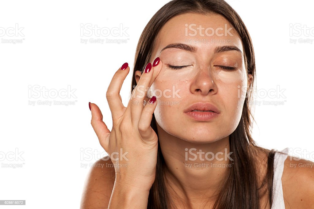 young women applied concealer around the eyes with her finger stock photo