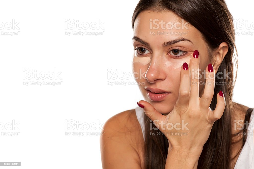 young women applied concealer under the eyes with her finger stock photo