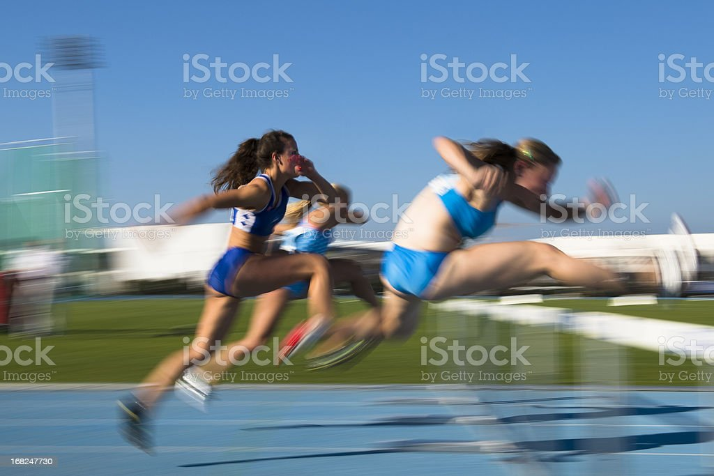 Young women at hurdle race 100 m stock photo