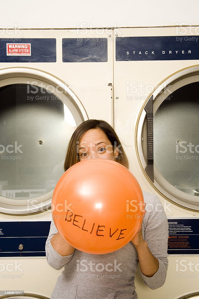 Young women blowing up a balloon at the laundromat. royalty-free stock photo