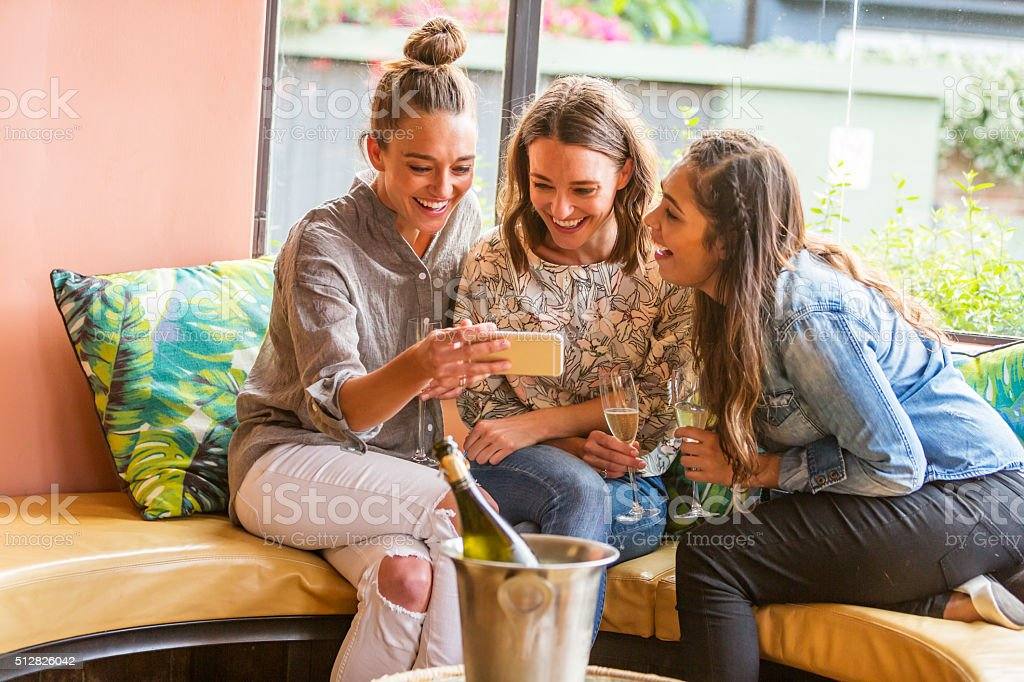 Young Women Celebrating and Laughing With A Phone and Champagne stock photo