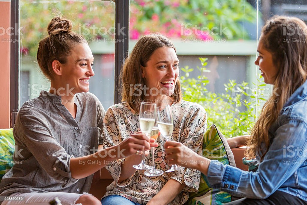 Young Women Celebrating With Champage in a Bar stock photo