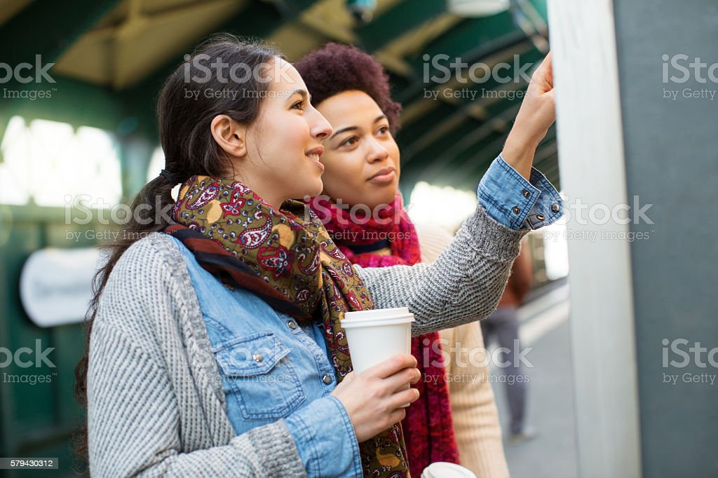 Young women checking route map on train platform stock photo