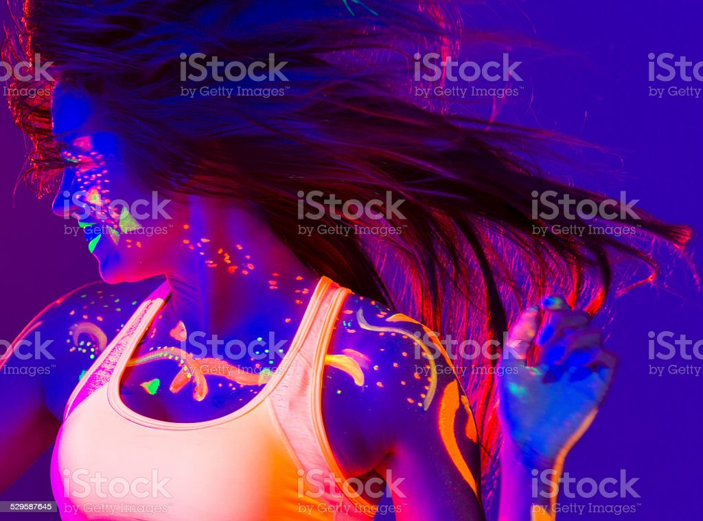 Young women covered with uv corol dancing stock photo