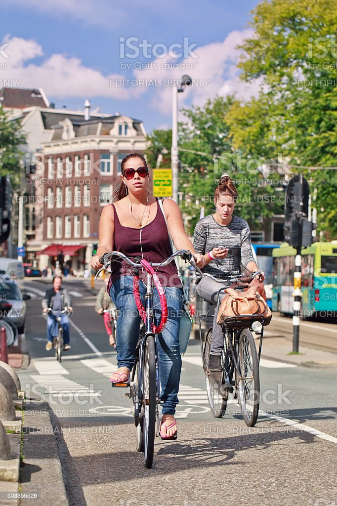 Young women cycling in a sunny Amsterdam city center stock photo