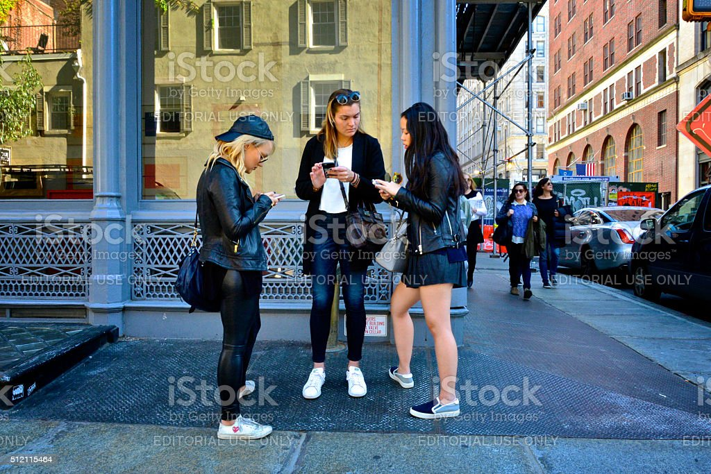 Young Women Discussing Smartphone Communications, SoHo, New York City stock photo