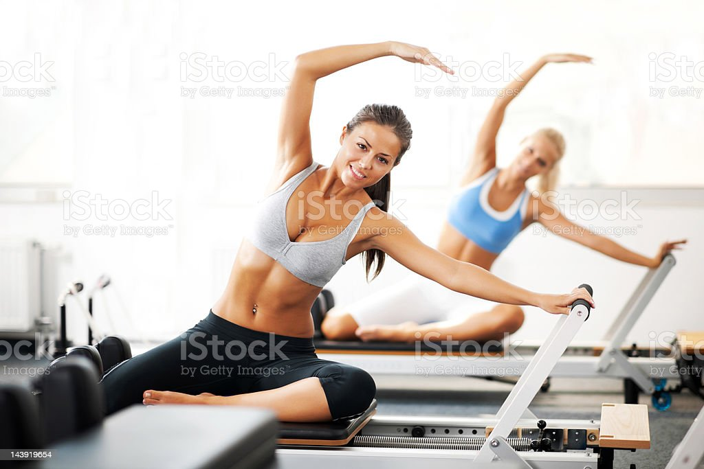 young women doing pilates exercises stock photo - Pilates Reformer Machine