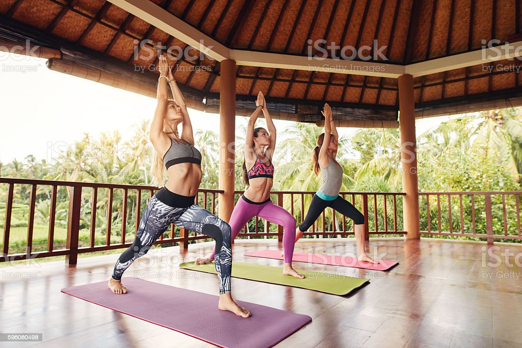 Young women doing the warrior pose in fitness class stock photo