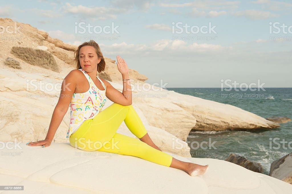 Young women doing yoga by the sea - Marichyasana stock photo