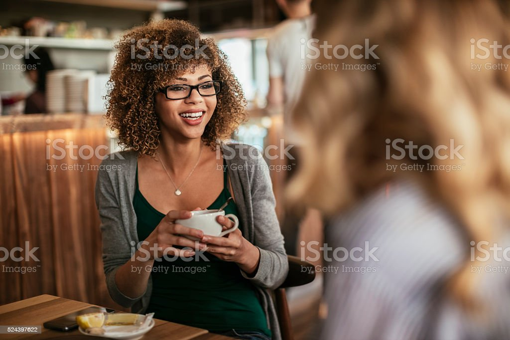 Young women drinking coffee at a cafe stock photo