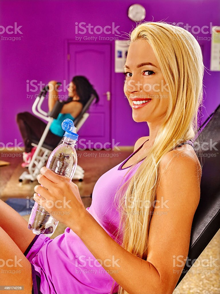 Young women drinking water in sport gym stock photo