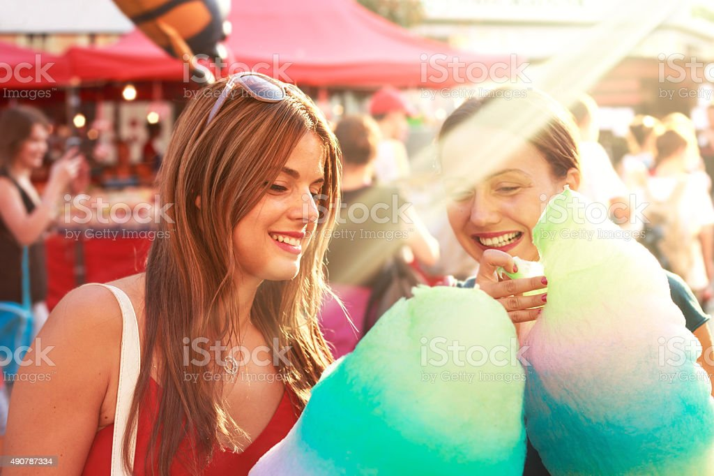 young women eating cotton candy and enjoying outdoor stock photo