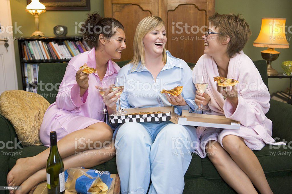 Young women eating pizza together in their pyjamas stock photo