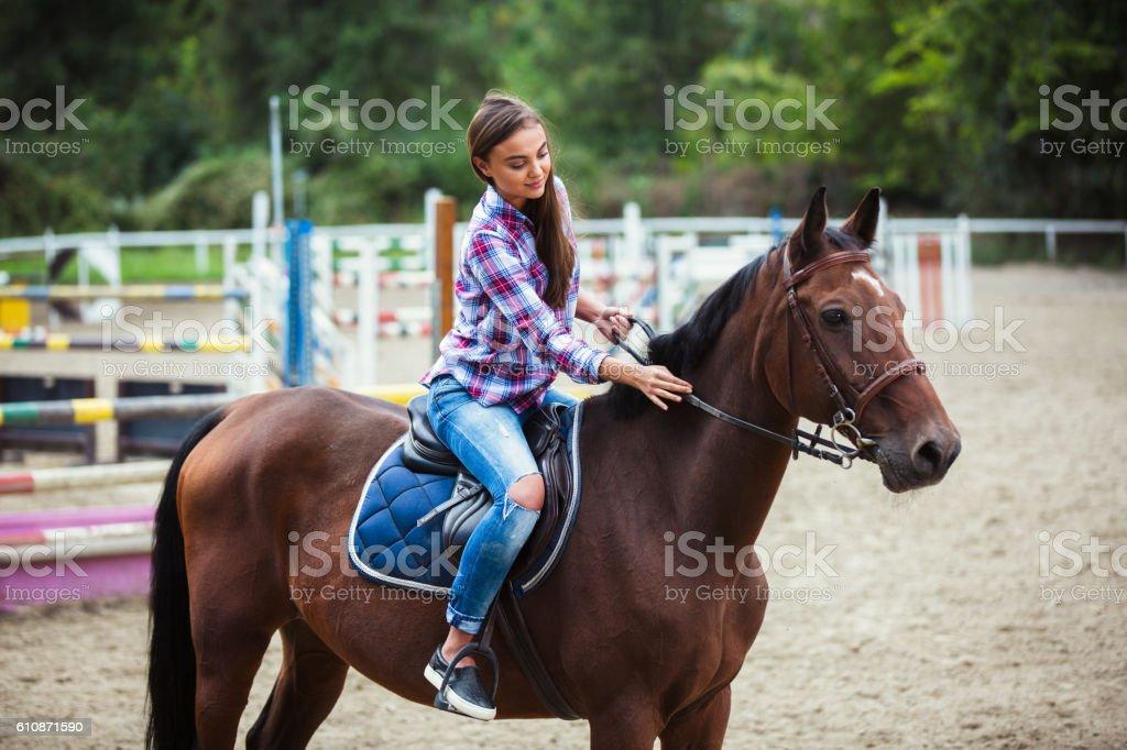 Young women enjoying horseback riding. stock photo