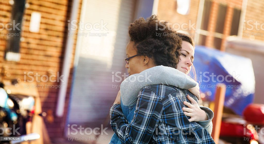 Young women forgiving each other with a hug stock photo