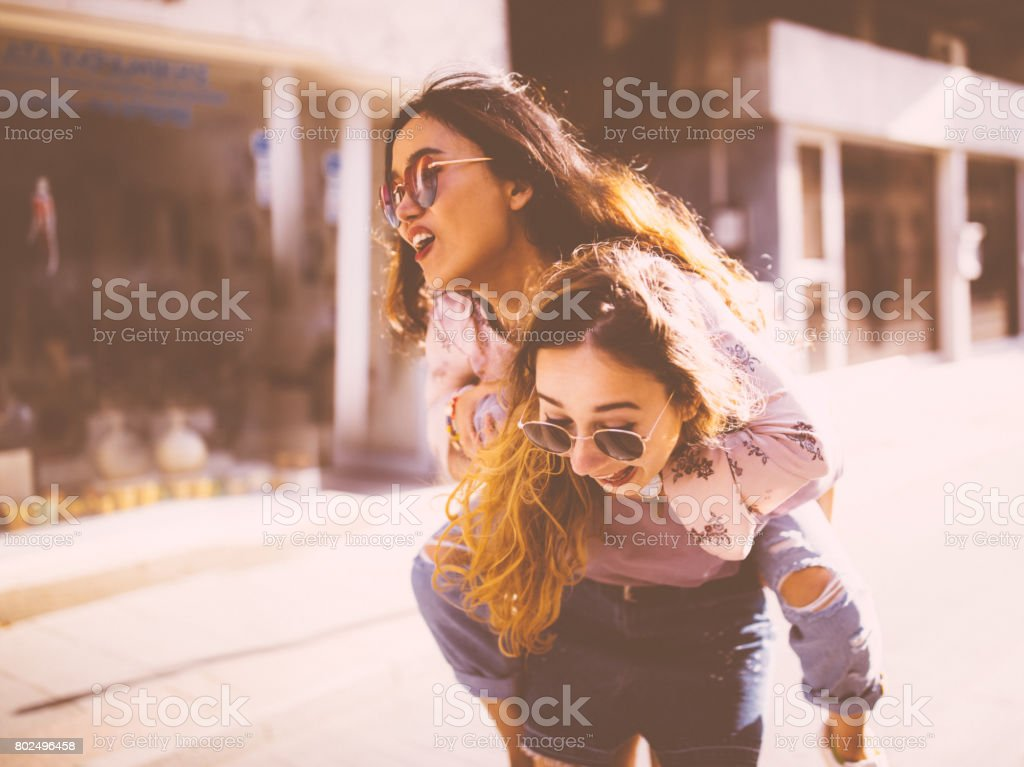 Young women giving a piggyback ride in old city streets stock photo