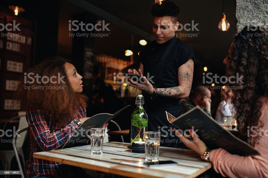 Young women giving order to a waiter at cafe stock photo