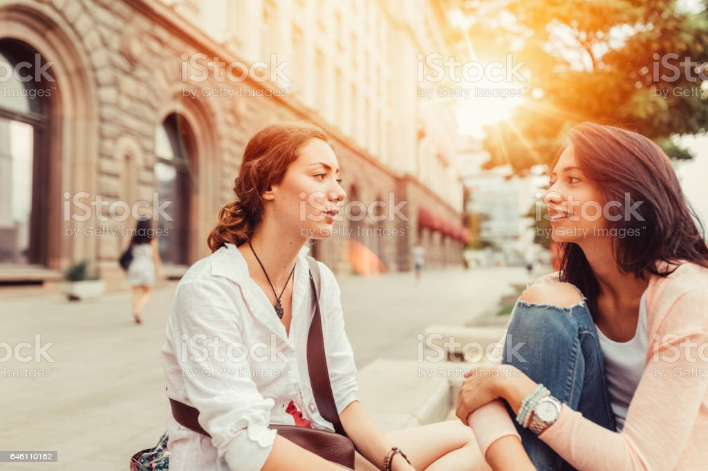 Young women gossiping outside stock photo