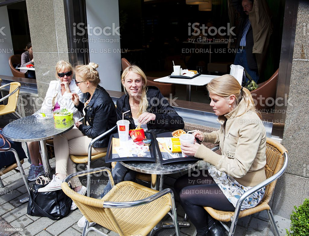 Young women having a meal on the sidewalk outside McDonalds. stock photo