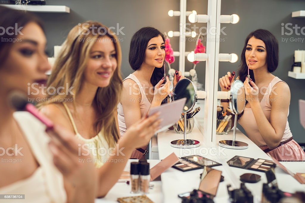 Young women having beauty treatment in make-up studio. stock photo