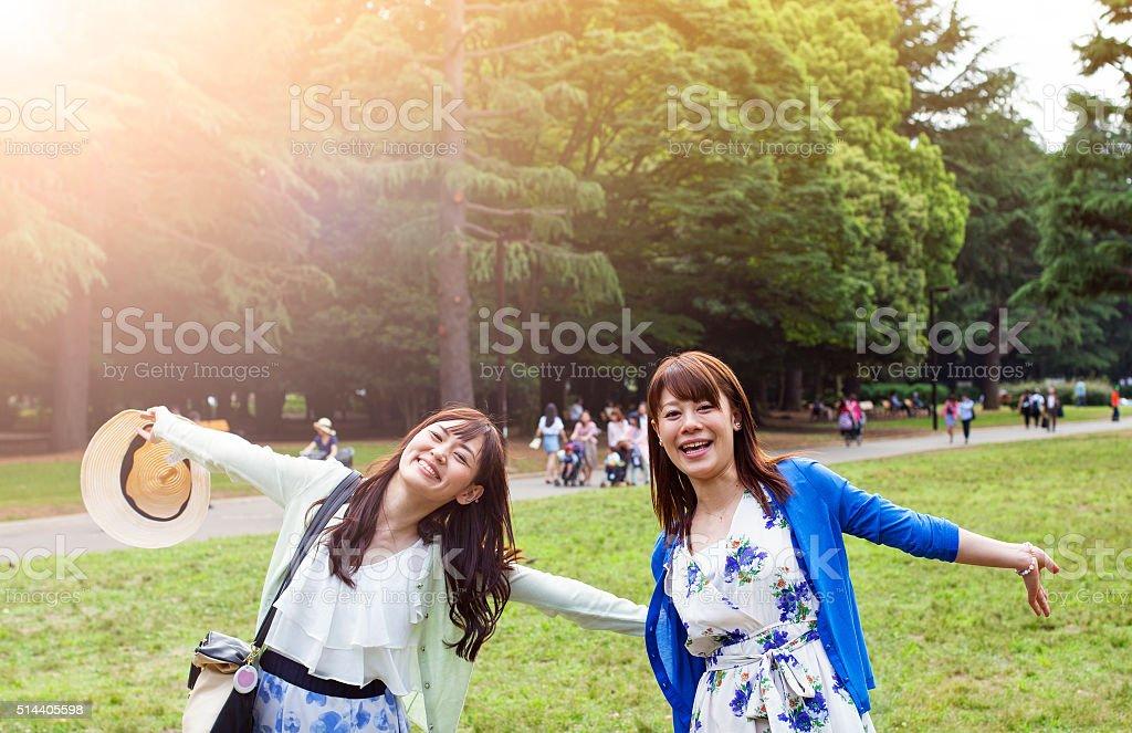 Young women having fun in city park, Tokyo. stock photo