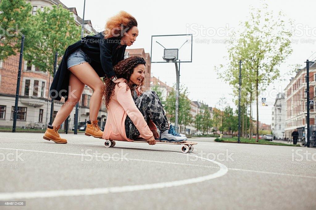 Young women having fun together with skateboard stock photo