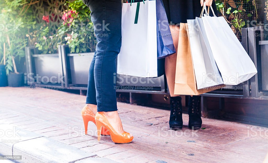 Young women holding shopping bags on street stock photo