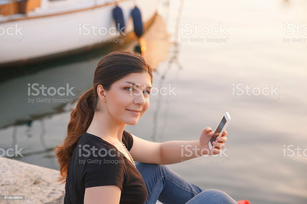 Young women holding using smartphone  Casual lifestyles Sunset at sea stock photo