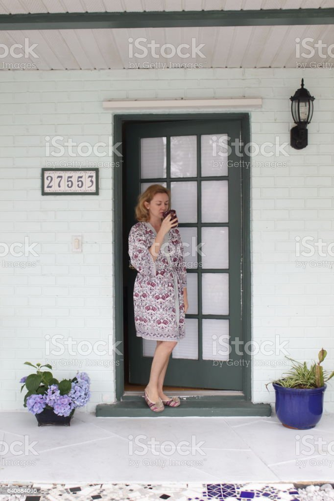 Young women in a bathrobe is standing on the porch of her home with the cup in her hand. stock photo