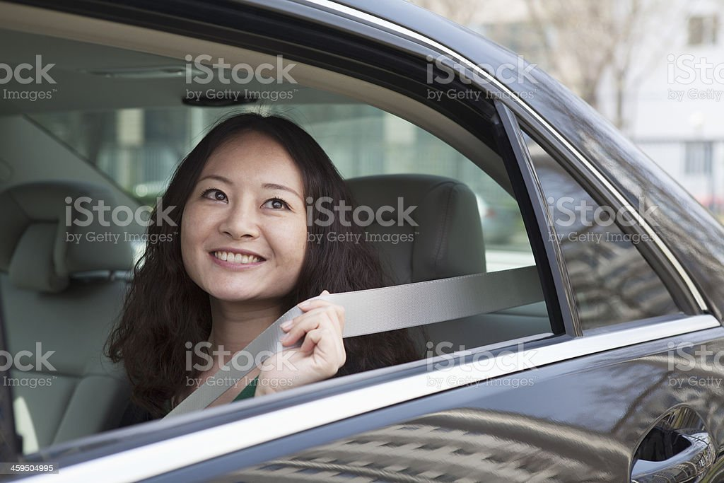 Young women in backseat of car fastening seat belt. stock photo
