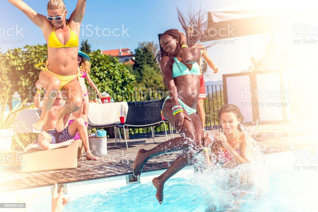 Young women in bikini jumping into pool stock photo