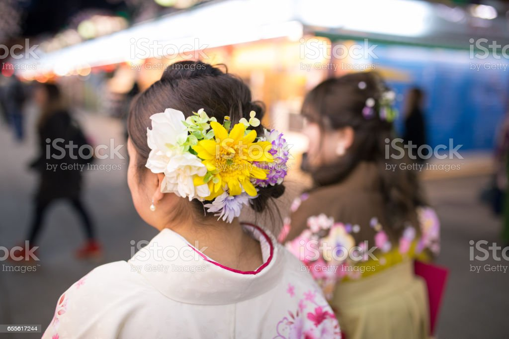 Young women in Hakama walking in traditional shopping street at night stock photo